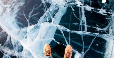 Man feet in boots on the Baikal ice