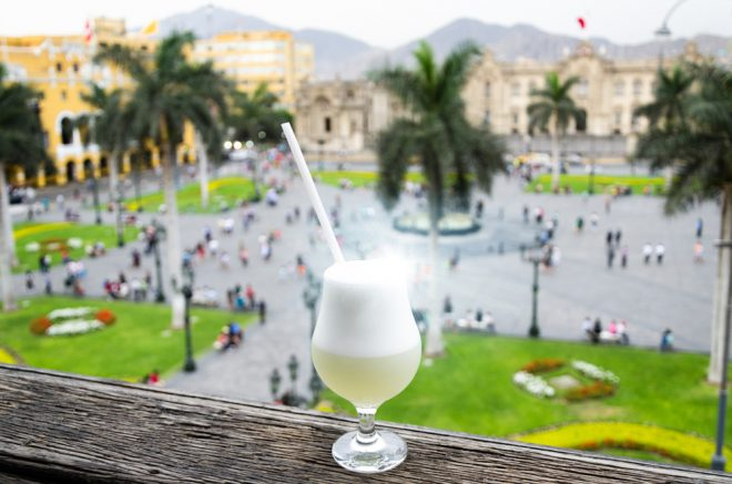 Vaso de pisco sour frente a la pintoresca plaza en Perú